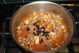 Adding the chick peas, raisins, apricots, cider vinegar and chicken broth for my Moroccan Pork Stew
