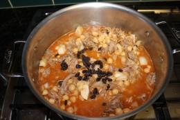 Adding the chick peas, raisins, apricots, cider vinegar and chicken broth for my Moroccan Pork Stew