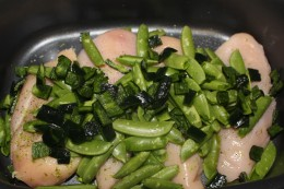 Adding the destemmed sugar snap peas and chopped poblano to the chicken for my Paleo Crock Pot Red Curry Chicken