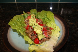 My Paleo Crock Pot Beef Fajitas served in a lettuce wrap with homemade guacamole and cherry tomatoes. This is how WE Paleo people so Taco Night