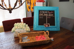 "Stache or Sash Gender Reveal Party. Everyone had to ""pick a side"" and choose a stache or sash (bow) pin to wear and cast their vote on the chalkboard. The mystery cakeballs were also displayed."