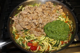Added the homemade pesto paste and browned pork sausage to the pan that has been sauteing your zoodles