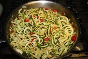 Added the perfectly spiraled and raw zucchini zoodles to the tomatoe and garlic sauce and cook on low while you make the homemade pesto