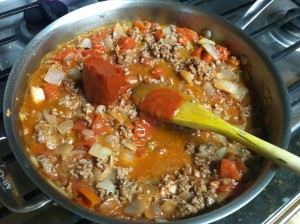 Adding the tomato paste to thicken the homemade sauce