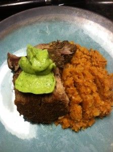 lose up of the pork shoulder pernil carnitas style served with avocado tomatillo sauce and chorizo no grain cauliflower rice